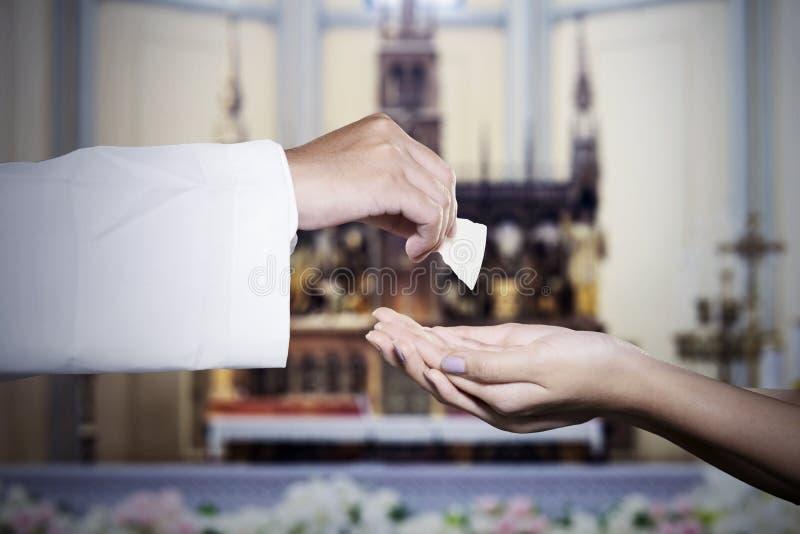 La femme obtient le pain de sainte communion d'un prêtre images libres de droits