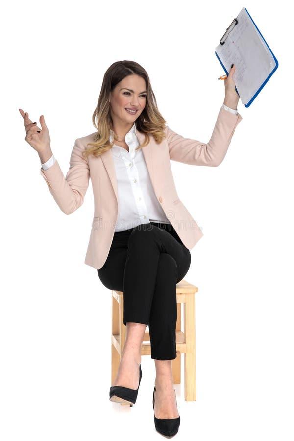 La femme occasionnelle futée assise curieuse tient le presse-papiers dans le ciel images stock