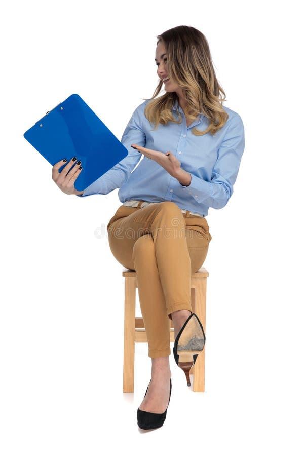 La femme occasionnelle futée assise curieuse tient le presse-papiers dans le ciel photos stock