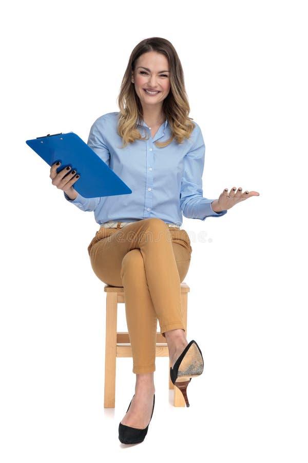 La femme occasionnelle futée assise curieuse tient le presse-papiers dans le ciel images libres de droits