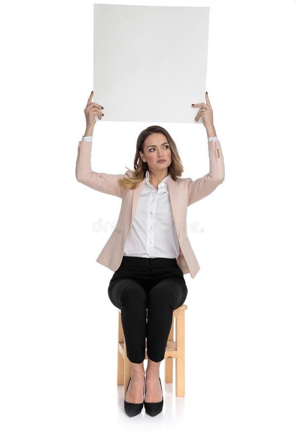 La femme occasionnelle futée tient le conseil et les regards vides pour dégrossir photo stock