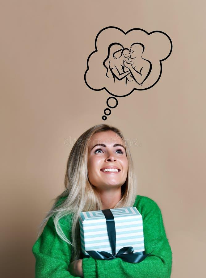 La femme occupée heureuse avec un boîte-cadeau dans des mains rêve de l'amour et de la famille photo libre de droits
