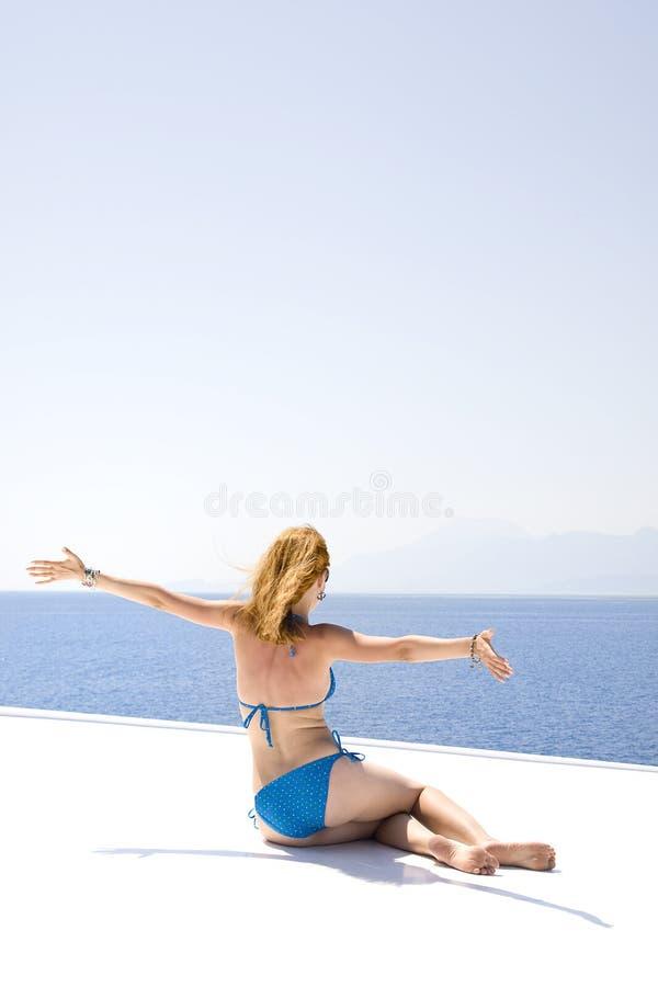 La femme a ouvert ses bras pour s'enrouler et la mer image libre de droits