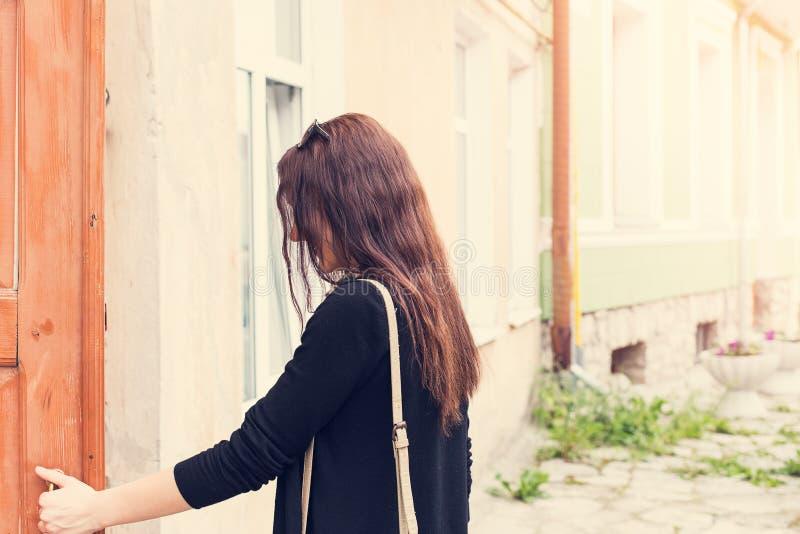 La femme ouvre la porte dehors image stock