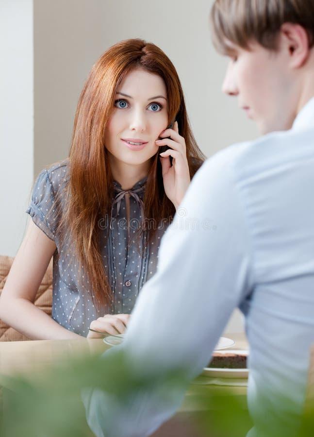 La femme parle du téléphone portable se reposant avec l'ami images stock