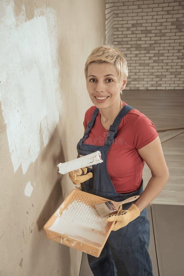 La femme peint le mur photographie stock libre de droits