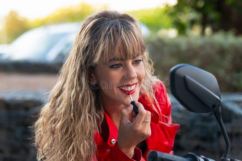 La femme peint ses lèvres avec le rouge à lèvres regardant dans le rétroviseur photo libre de droits