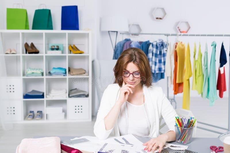 La femme pensant à sa mode projette dans un bureau créatif images stock