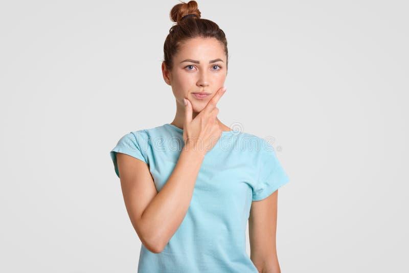 La femme perplexe réfléchie avec l'expression hésitante, menton de prises, habillé dans des vêtements sport, considère sur quelqu images libres de droits