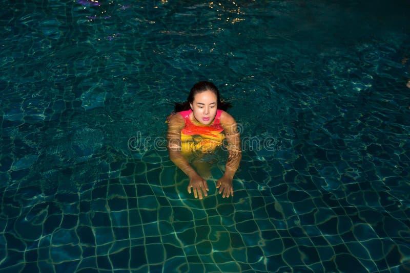 La femme a plaisir à jouer sa boule dans la piscine la nuit dans l'hôtel image libre de droits