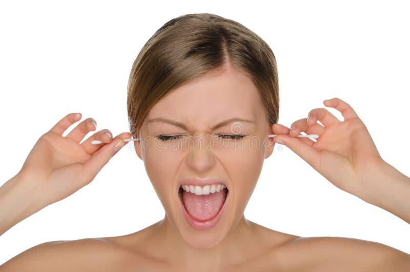 La femme pleurante nettoie des oreilles avec des bâtons de coton images stock