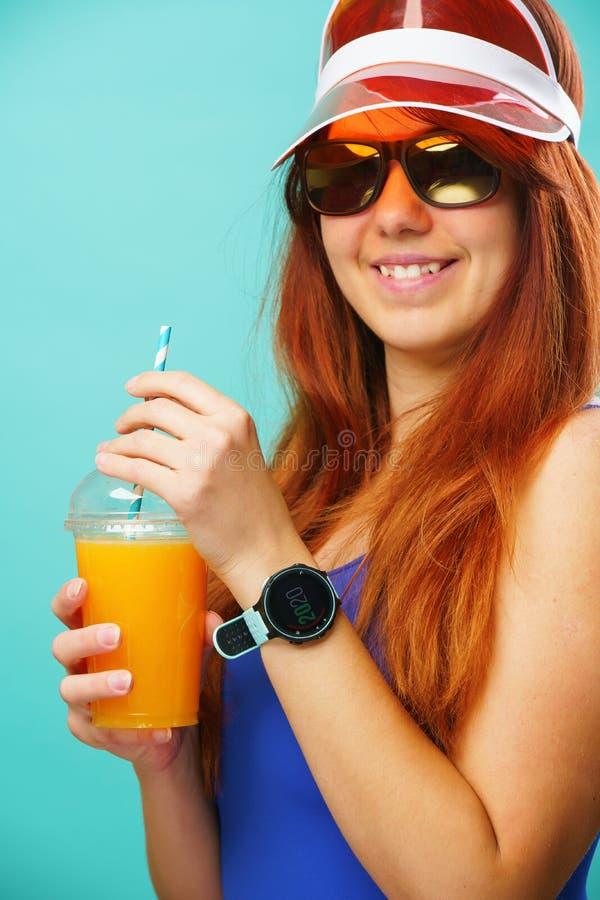 La femme portant des boissons d'un maillot de bain bleu, de chapeau et de lunettes de soleil fruit jus d'une tasse photographie stock