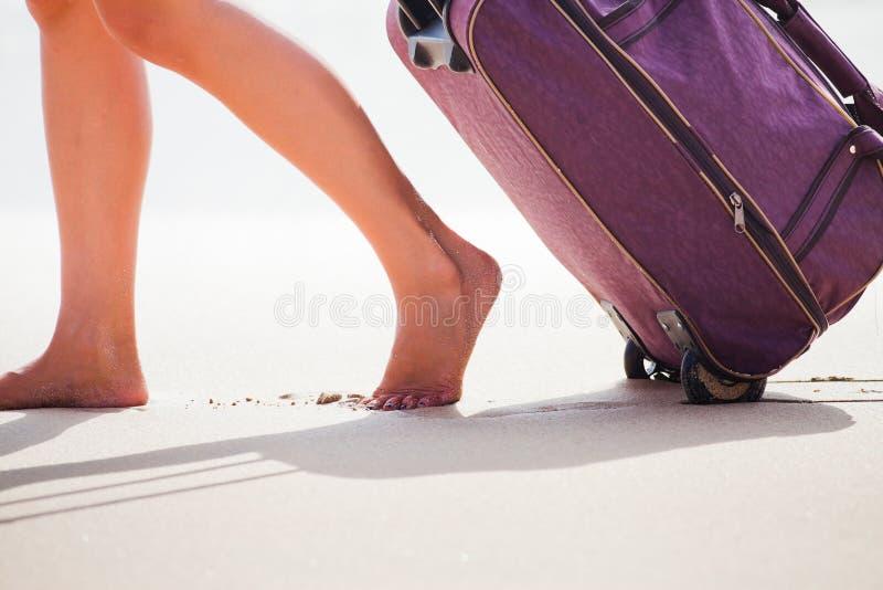 La femme porte votre bagage à la plage sablonneuse images stock