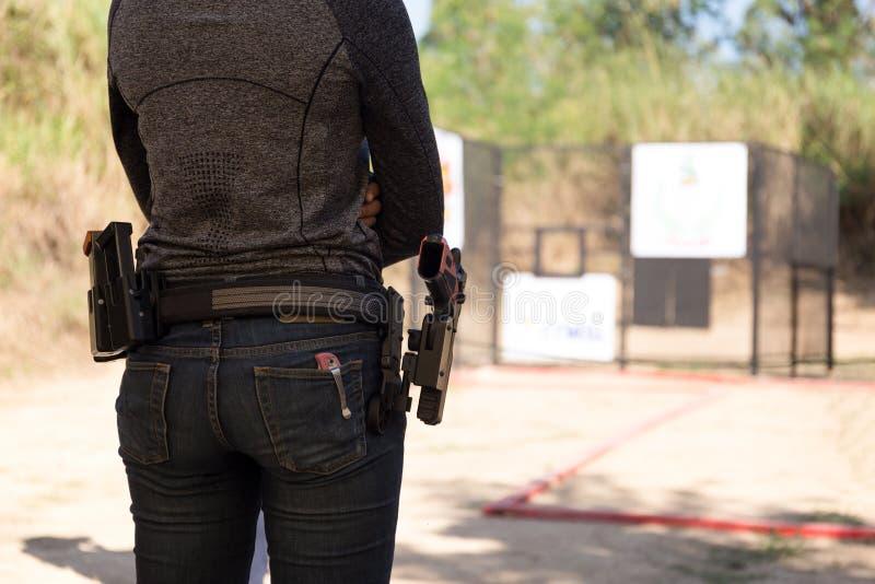 La femme portent le pistolet dans sa ceinture image stock