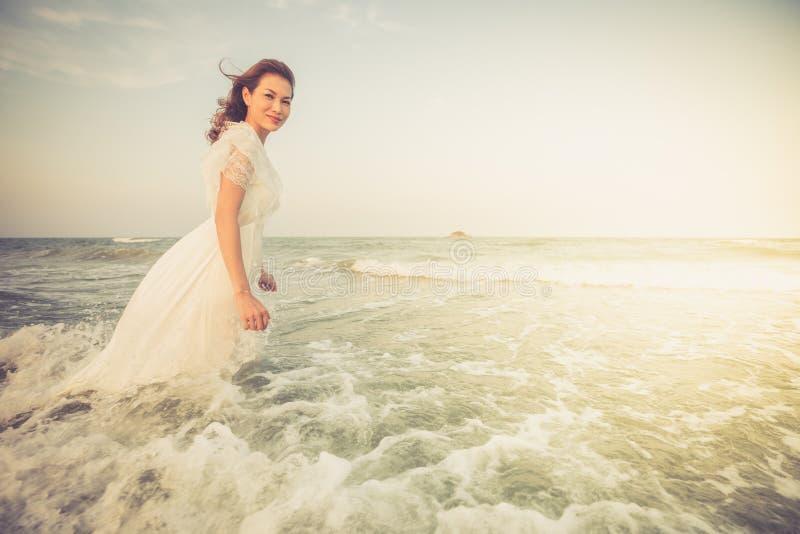 La femme portent la robe blanche seul tenant l'?vier en mer avec de l'eau et la vague la font humide mais se sentante bonne et he photographie stock