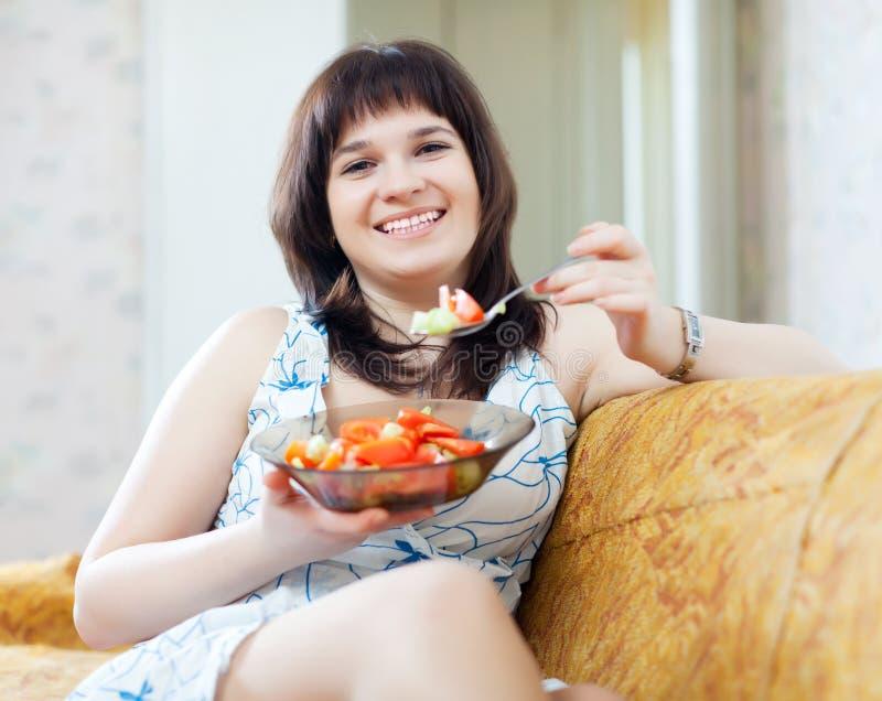 La femme positive mange de la salade de tomates images libres de droits
