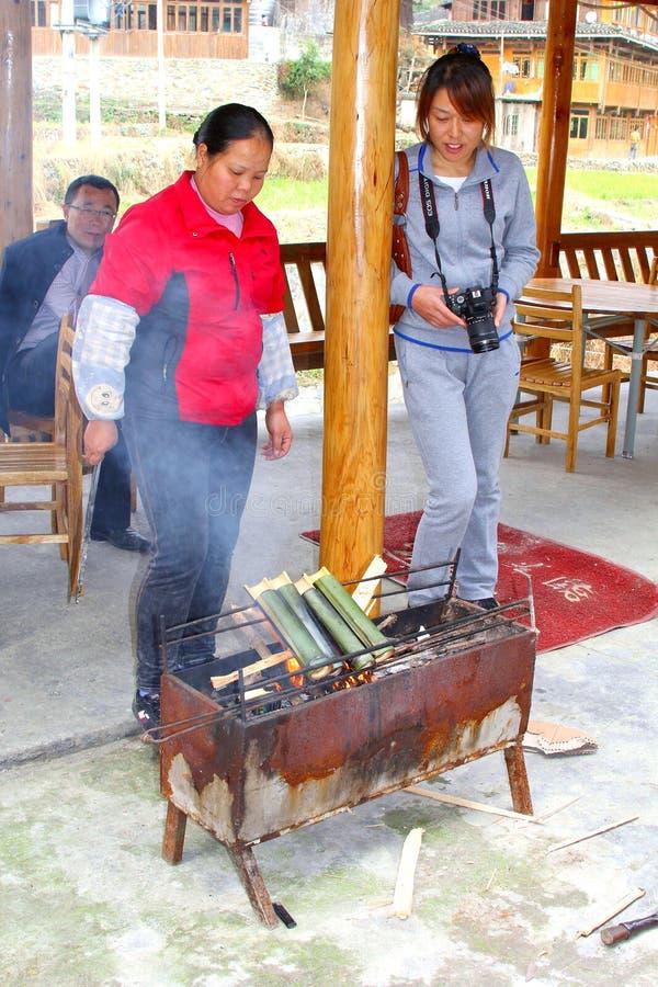 La femme prépare le riz collant dans des bâtons en bambou sur le barbecue, Chine photo stock