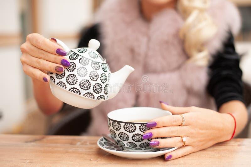 La femme préparent le thé sur le terace de barre tiennent la théière dans des ses mains dans l'oreille image libre de droits
