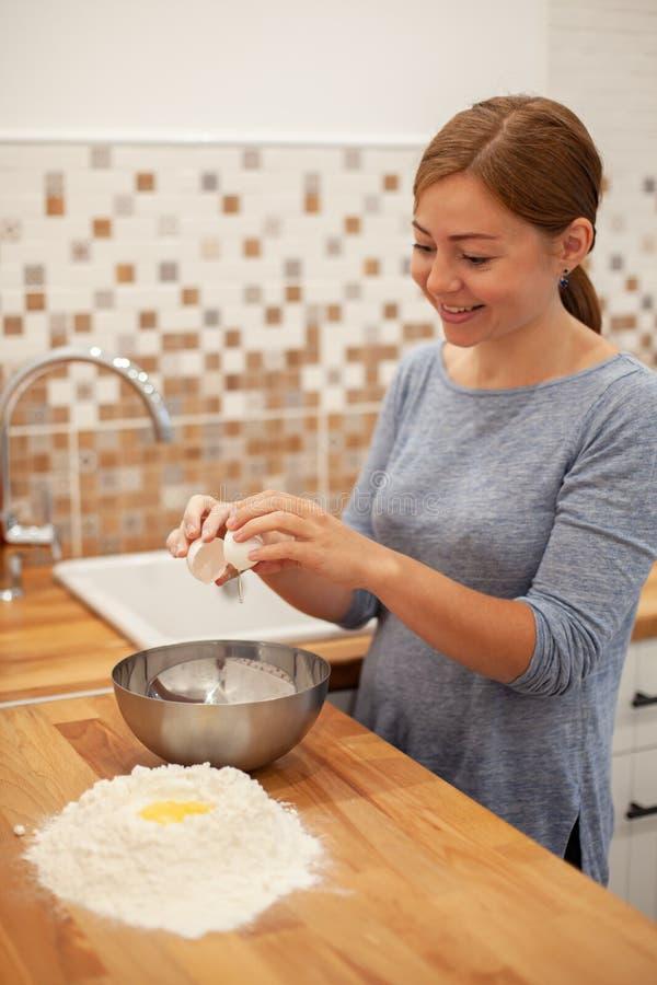 La femme préparent la pâte à tarte dans sa cuisine images libres de droits