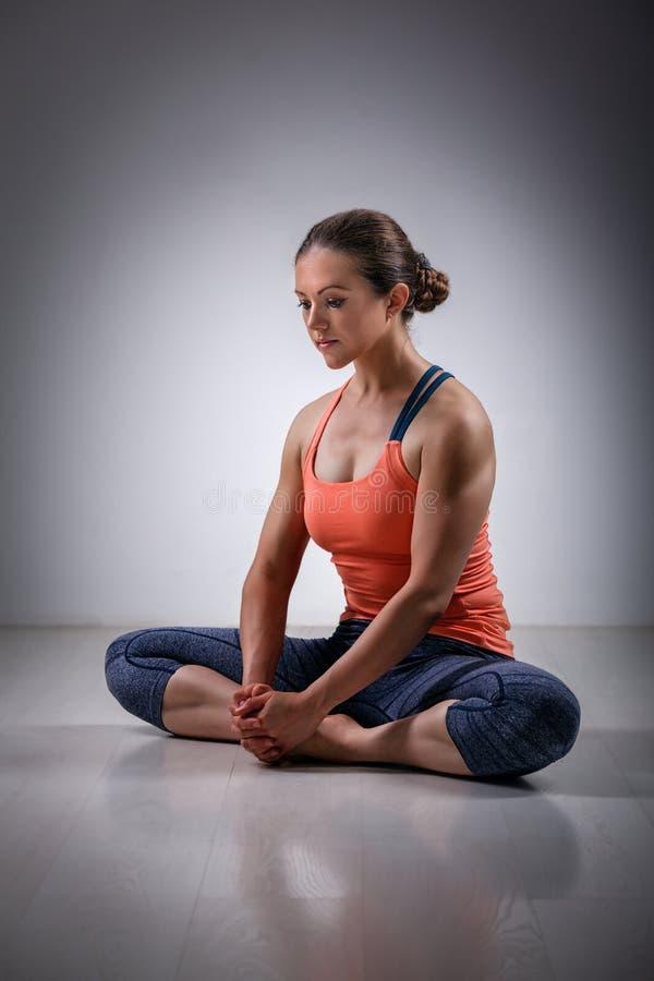 La femme pratique le konasana de Baddha d'asana de yoga photo libre de droits