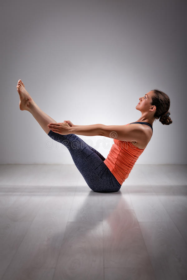 La femme pratique le navasana de Paripurna d'asana de yoga images libres de droits