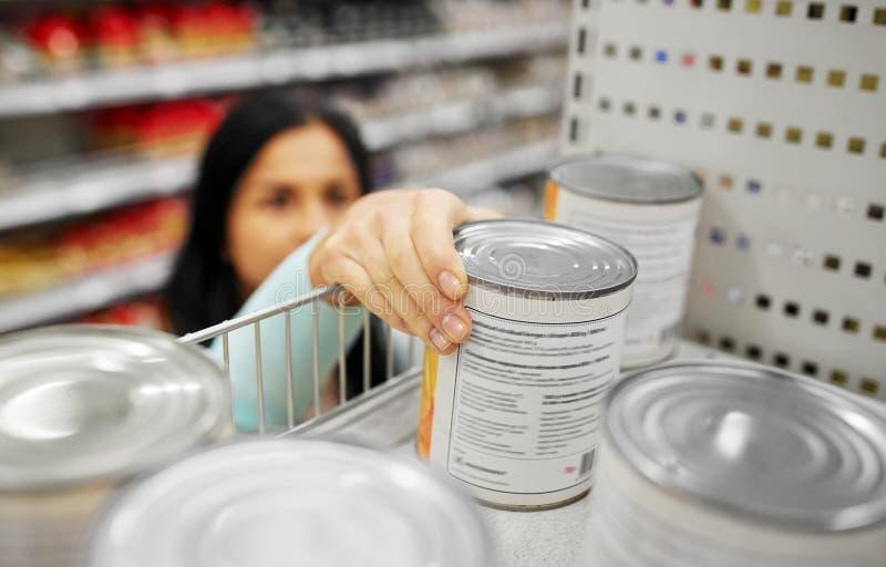 La femme prenant peut avec la nourriture de l'étagère à l'épicerie images stock
