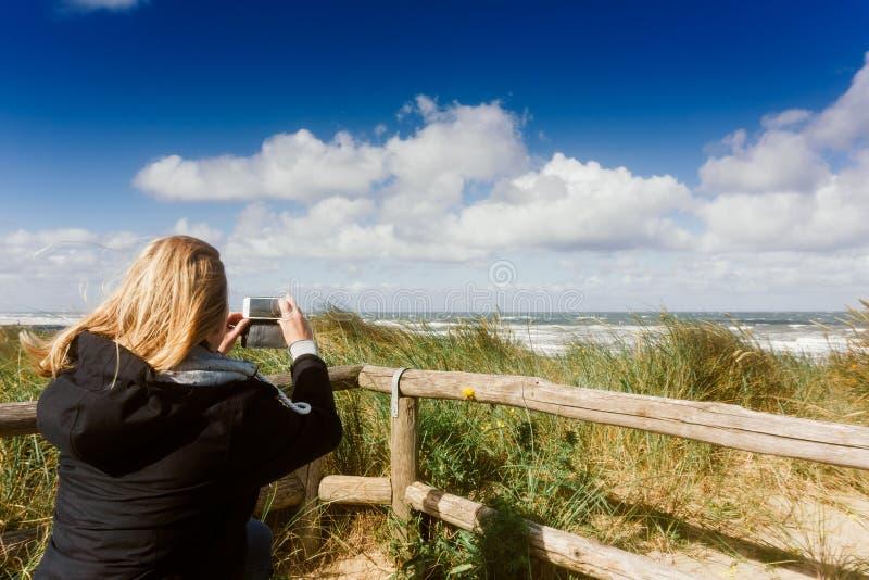 La femme prend à un instantané de la plage la mer et les dunes images libres de droits
