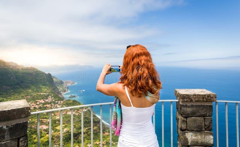 La femme prend la photo du paysage de bord de la mer photographie stock libre de droits