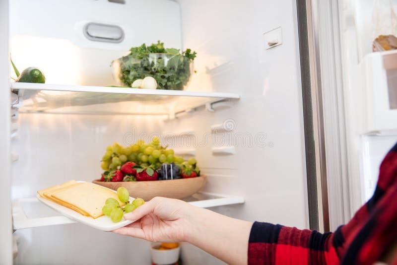 La femme prend le fromage du réfrigérateur images libres de droits