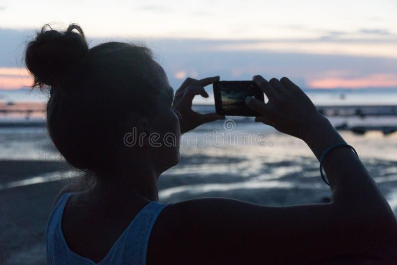 La femme prend un coucher du soleil au-dessus de la mer sur un appareil-photo de téléphone images stock
