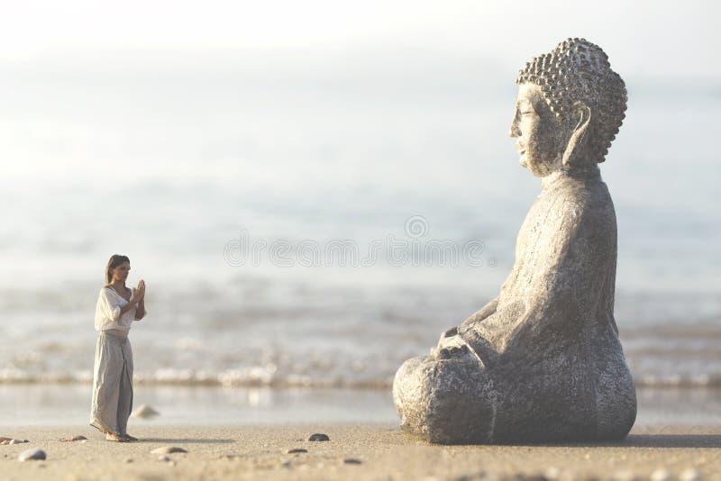 La femme prie méditer devant la statue de Bouddha images stock