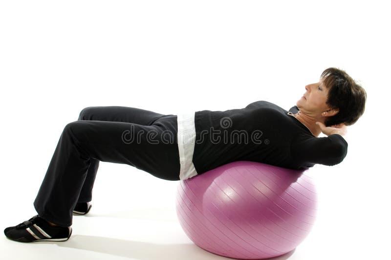 La femme que la bille de forme physique de formation de noyau se reposent se lève photographie stock libre de droits
