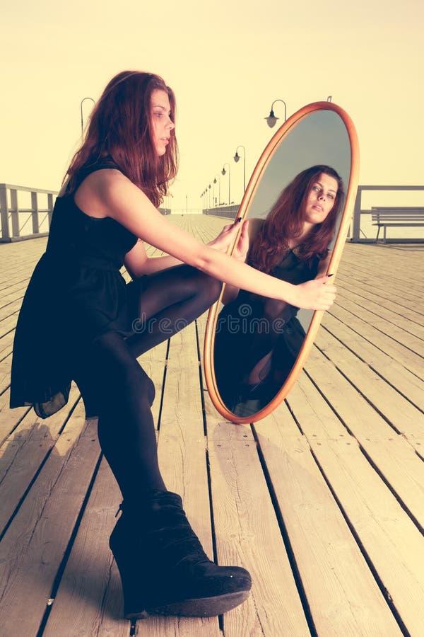 La femme réfléchie regarde la réflexion dans le miroir photo stock