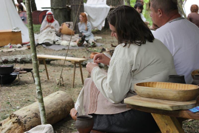 La femme répare son costume historique Nomades sur une halte dans la forêt image stock
