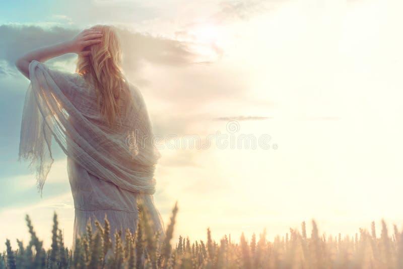 La femme rêveuse et belle regarde l'infini pendant que le soleil se lève images stock