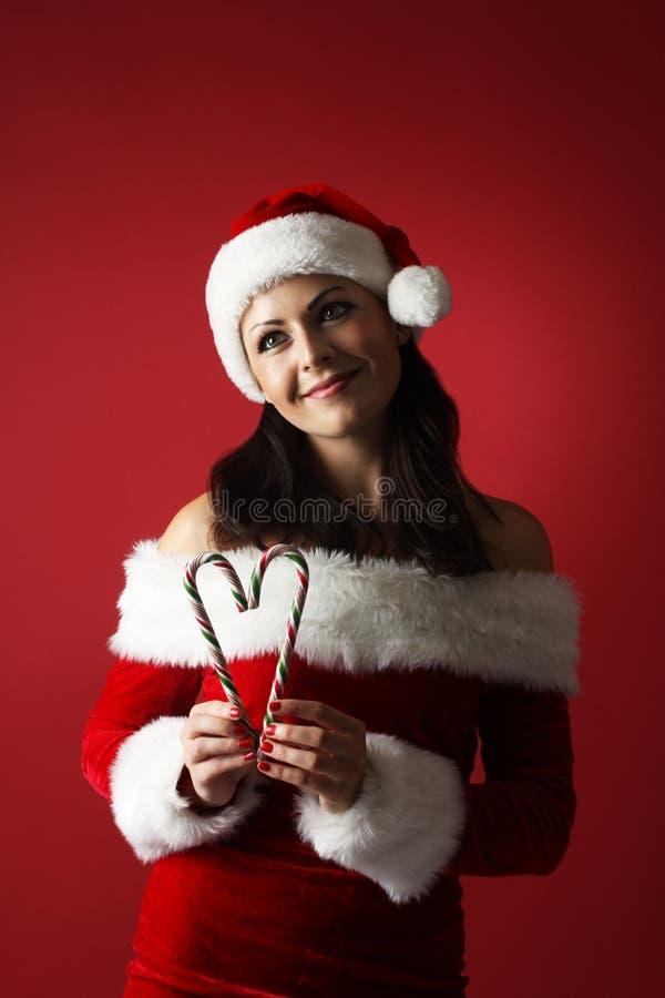 La femme rêveuse portant le père noël vêtx tenir le coeur de forme de canne de sucrerie sur le fond rouge image stock