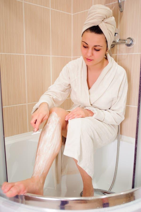 La femme rase sa jambe, belle femme après la prise de la douche de détente photo stock
