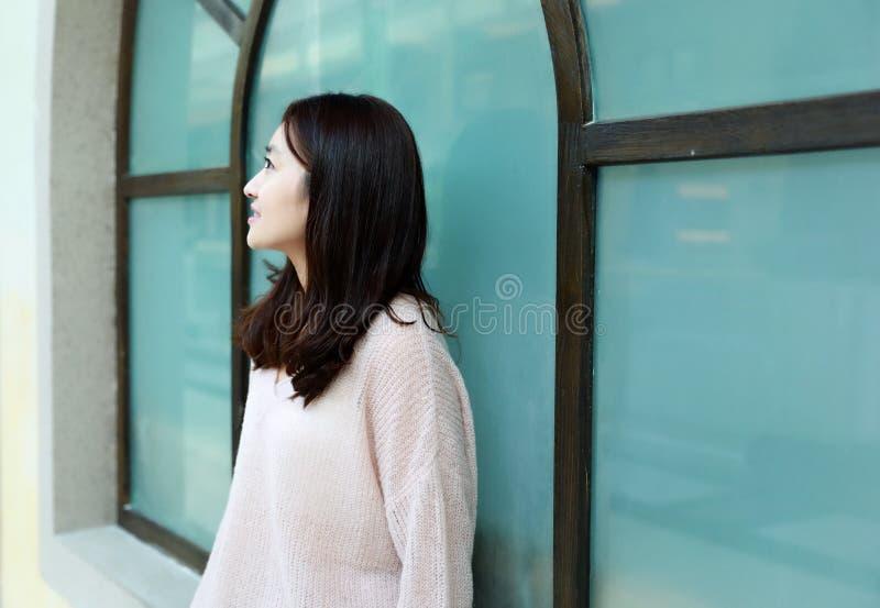 La femme regardant la boutique s'asseyent devant la fenêtre et le repos photos stock