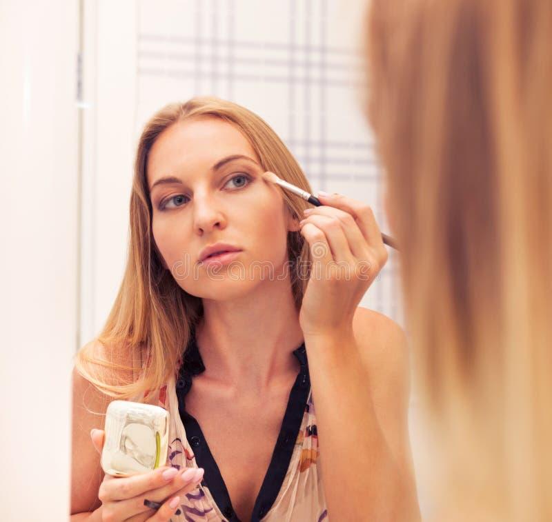 La femme regardant dans le miroir et mettant composent dessus photos stock