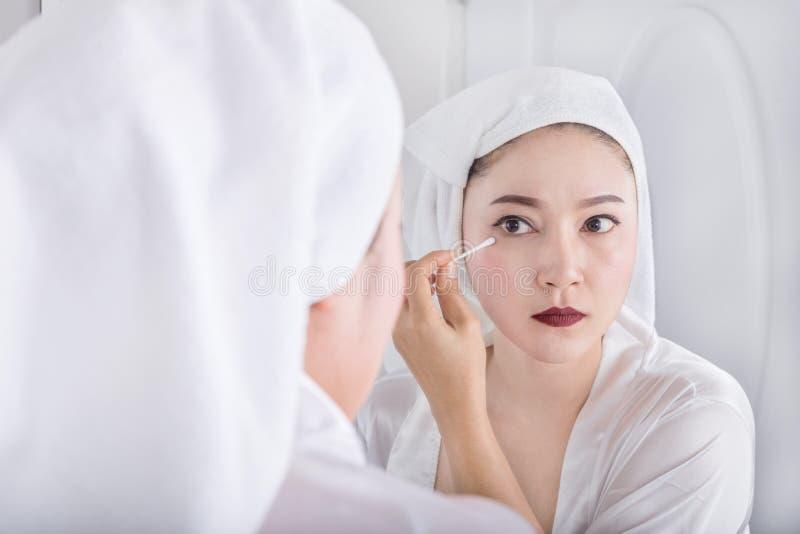 La femme regardant le miroir et enlèvent le maquillage près de l'oeil avec du coton photos stock