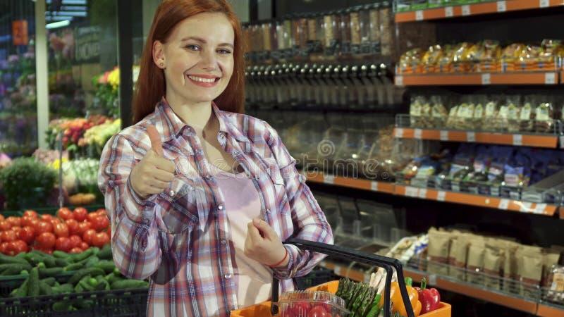 La femme regarde au-dessus de ses achats l'hypermarché photo libre de droits