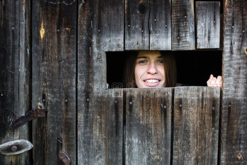 La femme regarde et sourit la petite fenêtre dans le hangar en bois image stock