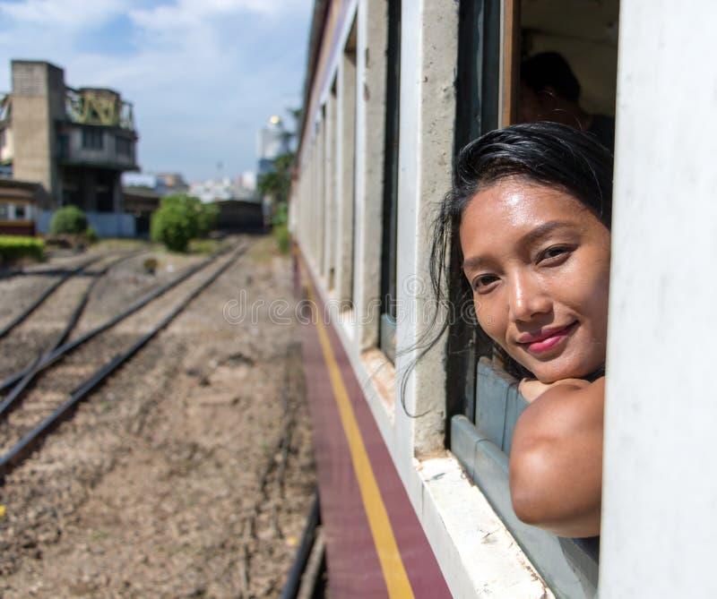 La femme regarde hors de la fenêtre d'un train mobile images stock