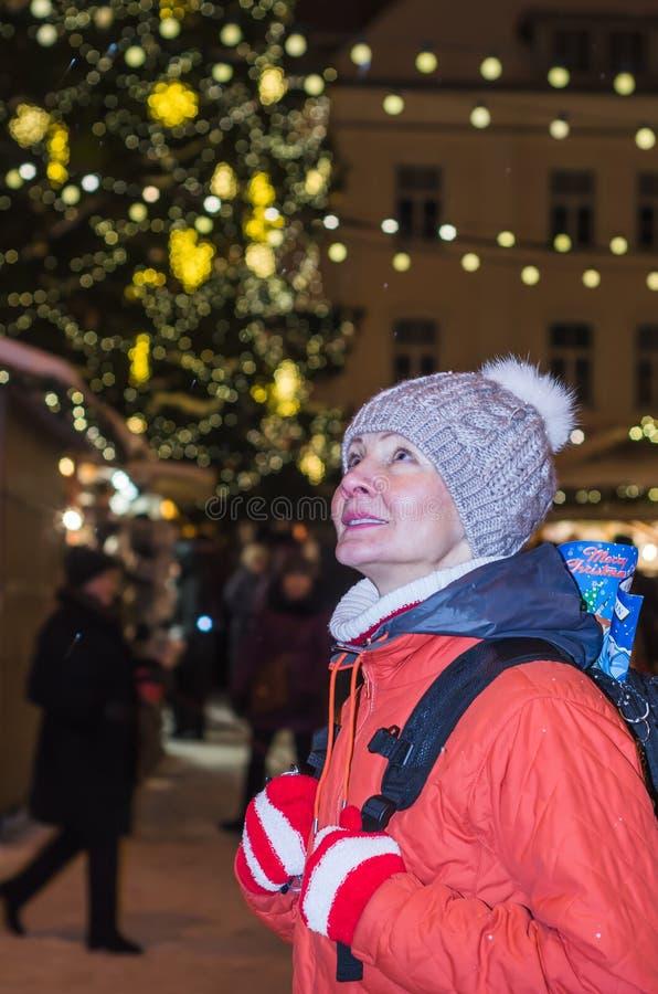 La femme regarde la ville décorée Hall Square de Noël à Tallinn images stock