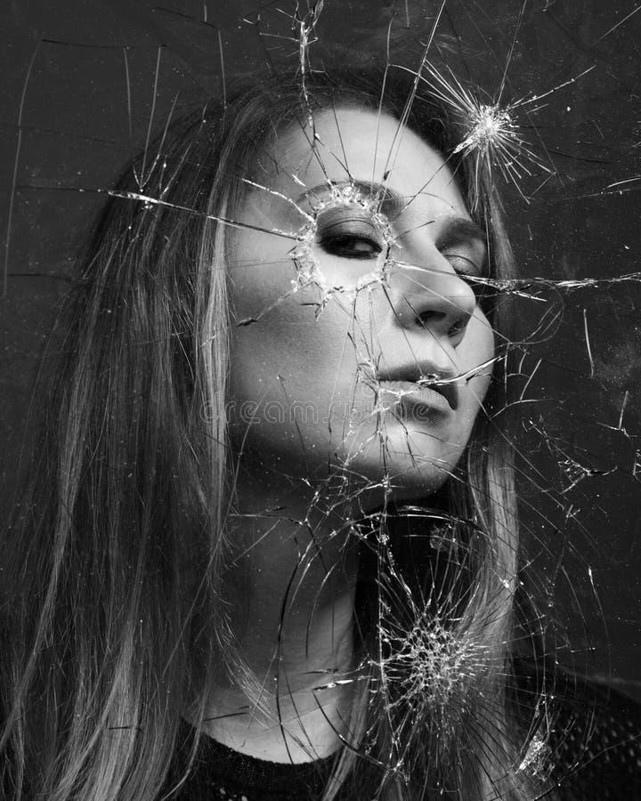 La femme regarde par le verre cassé Rebecca 36 photo libre de droits