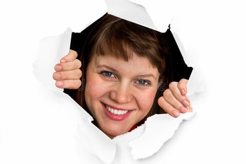 La femme regarde par un trou en papier déchiré images stock