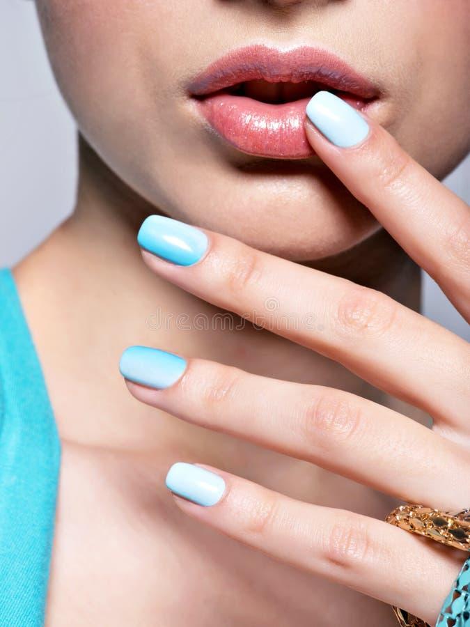 La femme remet des bijoux de bleu de mode de manucure d'ongles La femelle remet des WI photographie stock