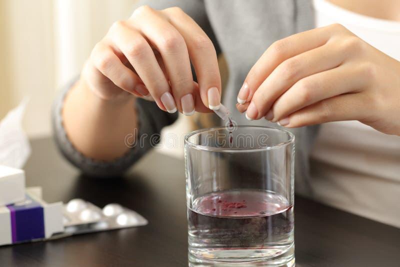 La femme remet dissoudre un contenu de capsule dans l'eau images stock