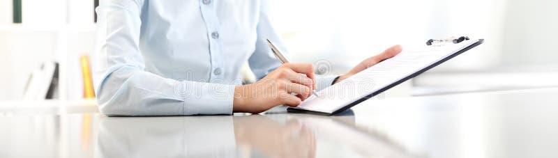 La femme remet l'écriture sur le presse-papiers avec un stylo, d'isolement sur le bureau photographie stock