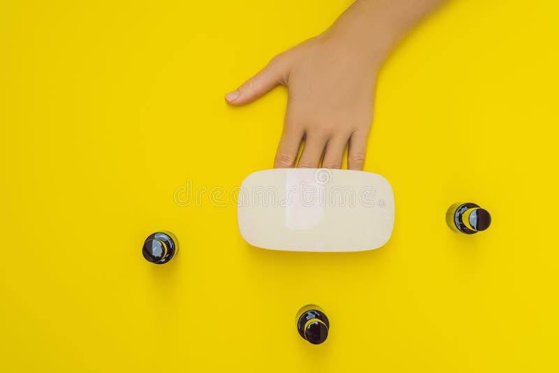La femme remet le soin Ongles manucurés dans la lampe UV Poli de gel de traitement de rayons Petits art d'ongle et affaires de ma photographie stock